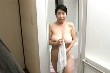 Mature Asian babe, Rumiko Yanagi with big tits gives handjob in bathroom