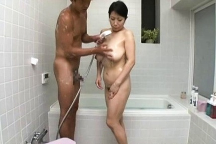 Mature Asian babe, Rumiko Yanagi with big tits gives handjob in bathroom